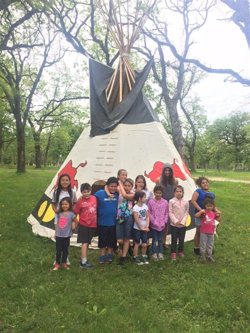 Students standing in front of a tipi